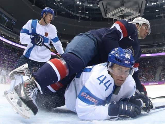 Ryan McDonagh, No. 27, of the United States falls on Kimmo Timonen, #44, of Finland in the first period of the Bronze Medal game Saturday at the Sochi Olympics.