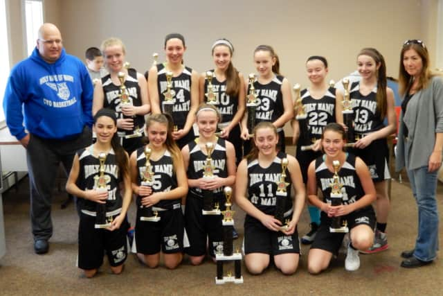 The Holy Name of Mary eight grade girls basketball team from Croton poses with its championship trophies. Player names are in the body of the story.