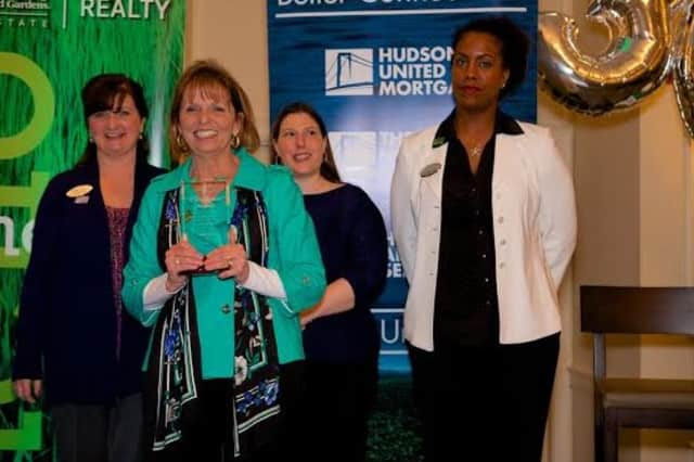 Janet Farsetta, vice president  of Relocation and Referrals Services of Better Homes and Gardens Rand Realty, accepts the award with Yvonne Regan, Erin Chambers and Monica Cooper.