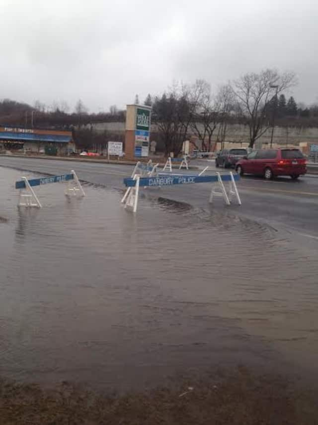 The road is flooded across all four lanes of Backus Avenue near the Danbury Fair Mall.