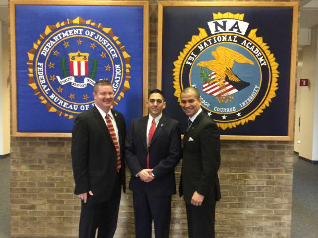 Bedford Police Chief William Hayes, left  and Lt. Melvin Padilla, right, congratulate Sgt. Andrew Bellantone, center at the FBI National Academy in Quantico, Va.