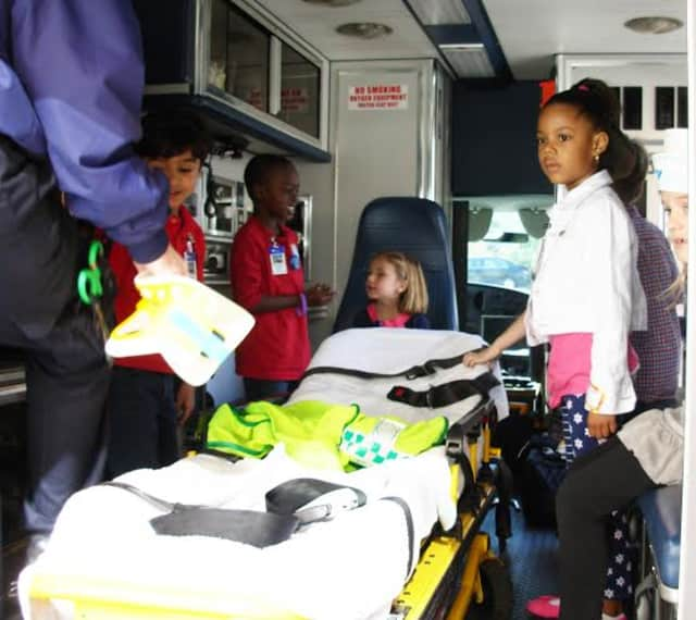 Greenwich Emergency Medical Services show children the inside of an ambulance and how to work a stretcher. A community fundraiser honoring EMS units from Harrison, Port Chester-Rye Brook and Greenwich is planned at Stanwich Club on Friday night.