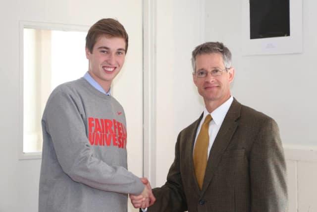 Darien's Benjamin Highton is going to play men's college soccer for Fairfield University. Highton, left, shakes hands with Head of School Andrew Vadnais
