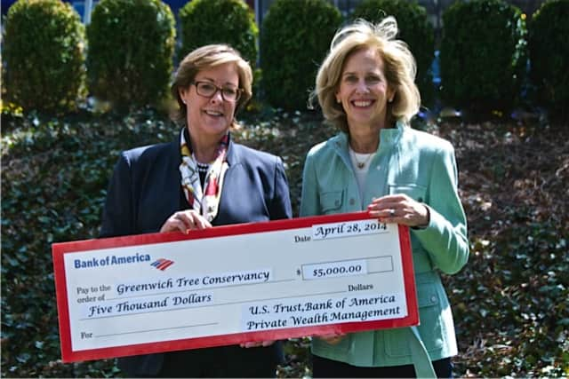Marion Schmeelk of U.S Trust, Bank of America, hands a sponsorship check for the Greenwich Tree Conservancy's Tree Party to Libby King, co-chairwoman of the Tree Party.