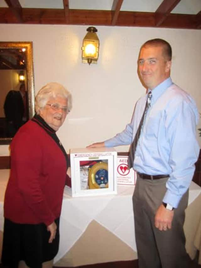 Elmsford Police Officer and PBA President Dennis Donohue presents a new defibrillator to Our Lady of Carmel School Principal Sister Mary Stephen on Tuesday, May 6.