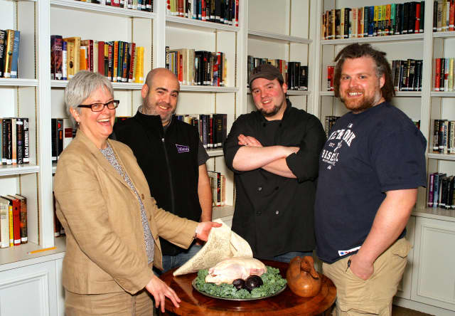 Grace Weber, executive director of Founders Hall, presents a fresh Pekin duck to Chefs Matt Storch, Forrest Pasternack and Jeff Taibe.