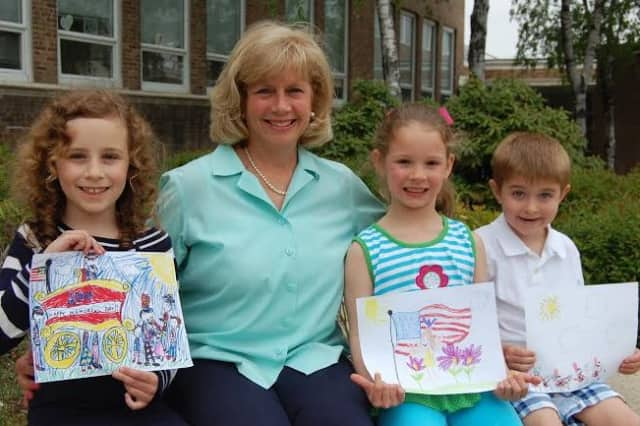 Winners of the second annual Memorial Day Parade Children's Drawing Contest showcase their artwork. From left are Alexandra Martin, Selectman Susan Marks, Caroline Gies and Ian Schneeberger.