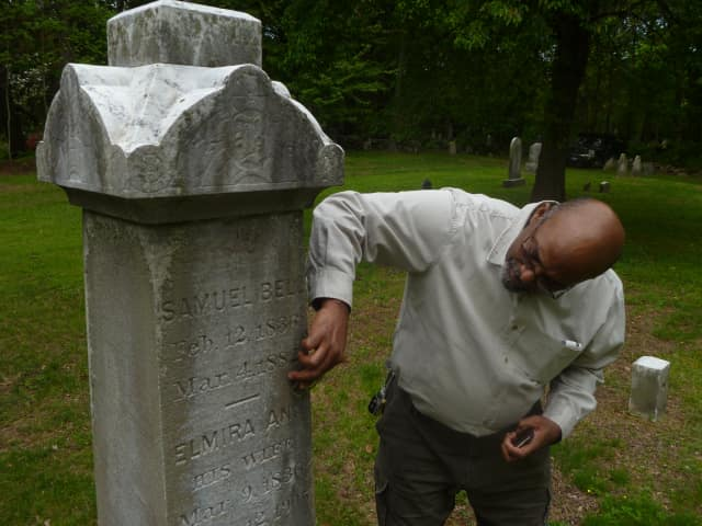 David Thomas scrapes off linchen, a fungus, off a grave stone as part of the effort to restore the African-American Cemetery in Rye.