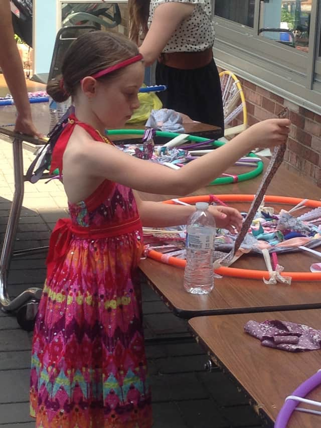 A young artist tries her hand at weaving a dream catcher at a prior event.