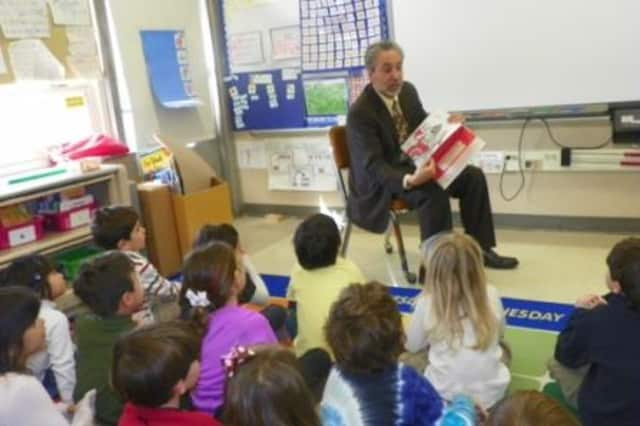 Harrison Schools Superintendent Louis Wool reads to students at Harrison Avenue Elementary School.