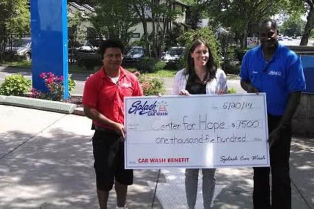 Amanda Romaniello, Family Centers' manager of clinical services for Darien and New Canaan, accepts a donation from Splash Car Wash's Oscar Moran, left, and Omar Locke.