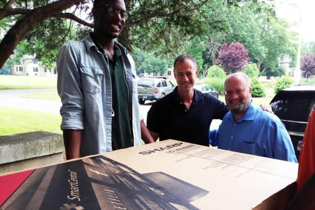 Dwight Thomas, Pleasantville Cottage School recreation staffer, Gregg Hammerschlag (who originally donated the TV to UJA-Federation to be used as the event's grand prize), and David Perlmutter transport a tv to Pleasantville Cottage School.