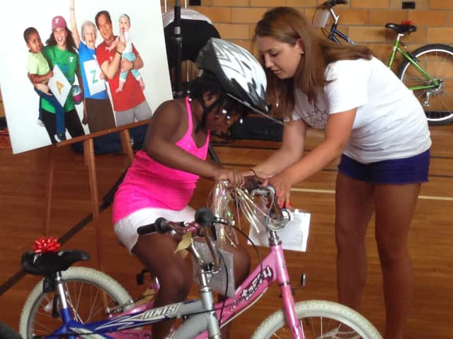 Lucia Villani helps Grace Bennett onto her new pink bike at the White Plains YMCA. The YMCA announced June 6 it will launch a new new initiative directed at helping teenagers to pursue active lifestyles.