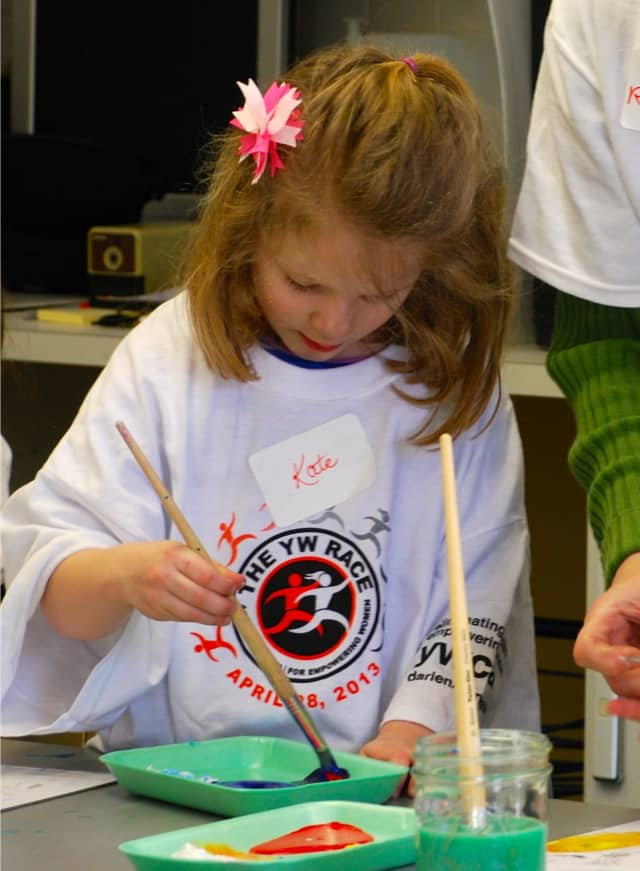 Kate Firgeleski enjoys mixing colors at the YWCA Darien/Norwalk Summer Children's Painting Workshop.