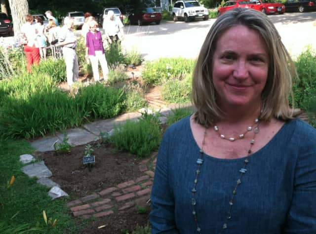 Leslie Nolan, executive director of the Wilton Historical Society, stands in front of the society's herb garden.