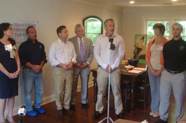 John Kydes and other Norwalk officials gather at his home to discuss the value of having a home energy efficiency assessment performed.