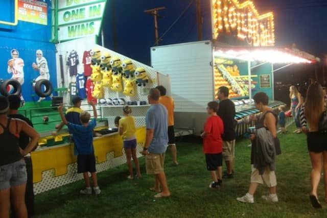 Fairgoers at the Norwalk Oyster Festival enjoy midway games in a previous year.
