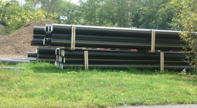 Pipe for the 3.5-mile gas pipeline in Wilton is stacked in a staging area. Work began in August and is expected to be completed by the end of November.