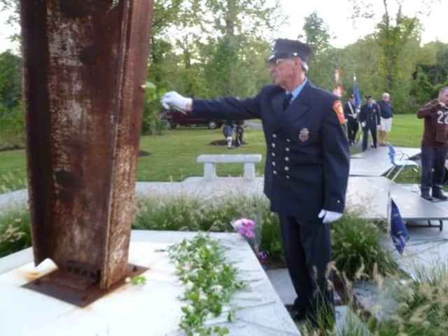 Many of those leaving roses at the foot of the Ridgefield memorial in a previous ceremony reached out to touch the steel.