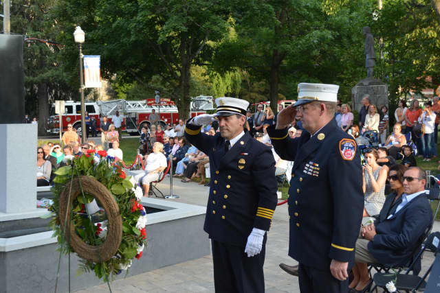 Firefighters give salutes at a prior 9/11 memorial service in Mount Kisco.