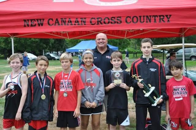 Coach Bill Martin celebrates with runners from the New Canaan Blazers youth cross country team after a strong performance at the Wilton Invitational.