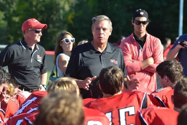 New Canaan football coach Lou Marinelli speaks with his team after winning his 300th career game Saturday against Greenwich.