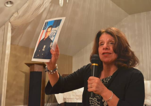 Carol Christiansen holds up a picture of her son, Erik at the Somers drug forum.