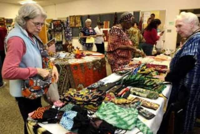 Woman examines some of the African handicrafts for sale at the 2013 bazaar. Tending the booth is Sister Marian Teresa Dury, who was a nurse in Tanzania for 24 years.