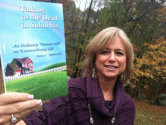 Wilton resident Anna Raimondi uses her spiritual psychic powers to help others. She's holding one of the two books she has written.
