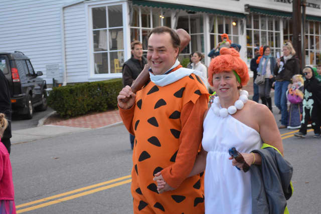 "(From 2014): Bedford Hills residents Ryan Archer and Laurie Kelleher march in the Katonah Halloween parade. They are dressed as Fred and Wilma from ""The Flintstones."""