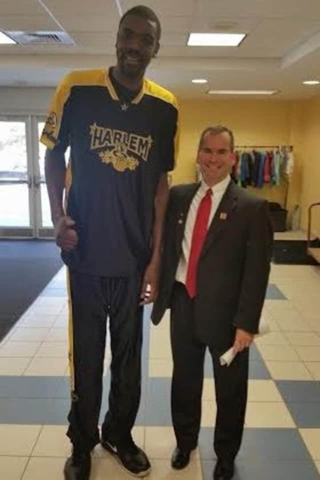 Rotary president Eric Lebenson stands with a Harlem Magic Masters player.