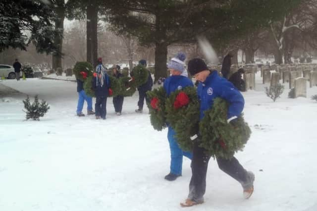 Volunteers brave the snow to lay wreaths on veterans' graves at the Wreaths Across America ceremony in Darien in a past year.