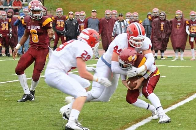 Zach Allen, 44, brings down a St. Joseph runner as David Strupp closes in during Saturday's game.