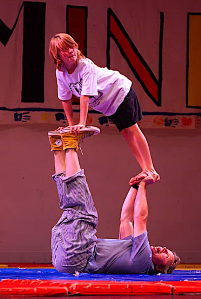 Kevin O'Keefe holds up a young volunteer during a presentation of Circus Minimus.
