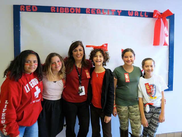 John Jay Middle School SADD Club members Andreya Pastrana, Ariella Mendez, adviser Tina Russo, Amelia Egeler, Emma Hinkley and Melanie Kardos pose in front of the school's Red Ribbon Week Reality Wall.