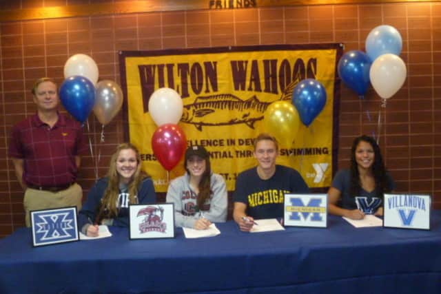 Swimmers for the Wilton Wahoos, from left, Maggie Kauffeld, Courtney Gilroy, Stephen Holmquist and Samantha Cheruk sign letters of intent to college programs. Randy Erlenbach, the team's Director of Aquatics, watches them sign the letters.