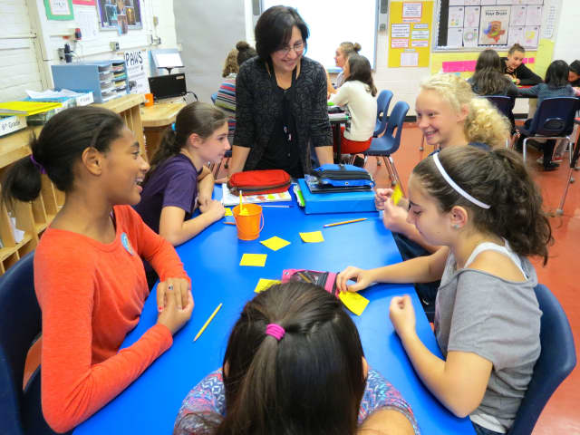 """Pierre Van Cortlandt media literacy teacher Johanna Mustacchi works with Pierre Van Cortlandt Middle School seventh-graders to brainstorm ideas about respect as they prepare storyboards about Langston Hughes' short story, """"Thank You, Ma'Am."""""""