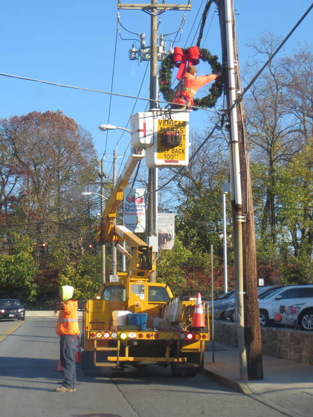 A city public works crew decorating a utility pole for the holidays along Purdy Street in Rye on Wednesday afternoon.