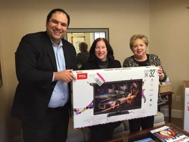 Donna Eastman receives her flat screen television from Houlihan Lawrence's Yorktown brokerage.