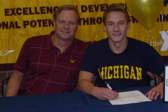 Wilton High School senior signs his letter of intent to attend Michigan. He is joined by Randy Erlenbach, the director of competitive aquatics for the Wilton Wahoos.