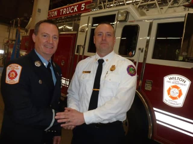 Greenwich Fire Department Assistant Fire Chief Robert Kick, at right, congratulates new Wilton Fire Department Lieutenant Jeffery Locher on his promotion Monday in a ceremony held in Wilton. Locher started his professional career in Greenwich.