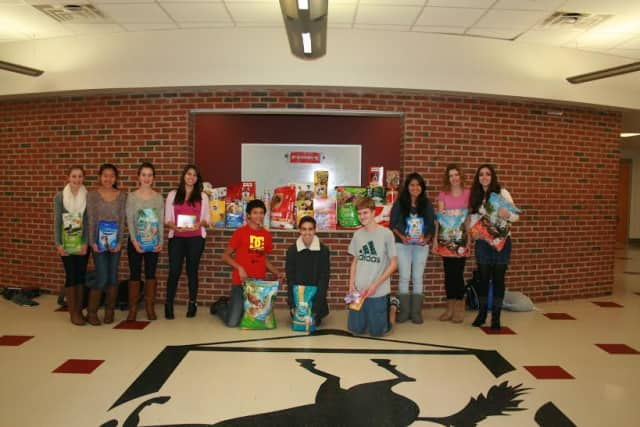 Students and club advisors collect more than 1,000 pet food items.