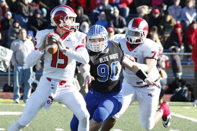 New Canaan quarterback Michael Collins looks for a receiver under pressure from Darien's Mark Evanchick.