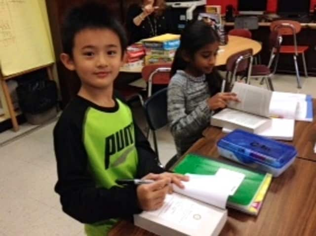 Todd Elementary School third-graders in Briarcliff Manor flipped through dictionaries gifted to them by the Briarcliff Manor Rotary Club.