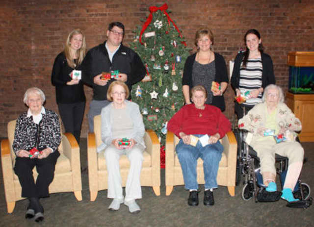 Pennyweights owners Kelly and Geoff Sigg present residents with some of the many donated gifts alongside Waveny's directors of therapeutic recreation, Patty Pasquarella and Lauren Elker.