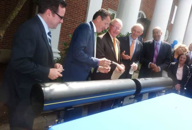 Gov. Dannel P. Malloy, second from left, jokes with Wilton First Selectman Bill Brennan, center, after they and other officials signed an 8-inch polyethylene pipe during a press conference Aug. 4 announcing the expansion of Yankee Gas into the town.