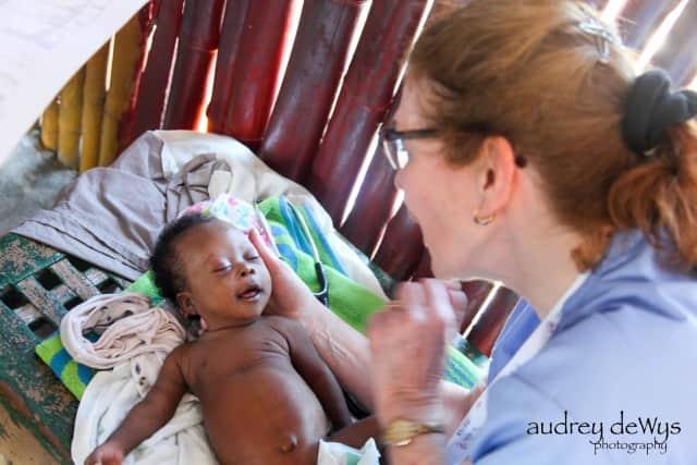 Nurse Judy McAvoy examines a baby.