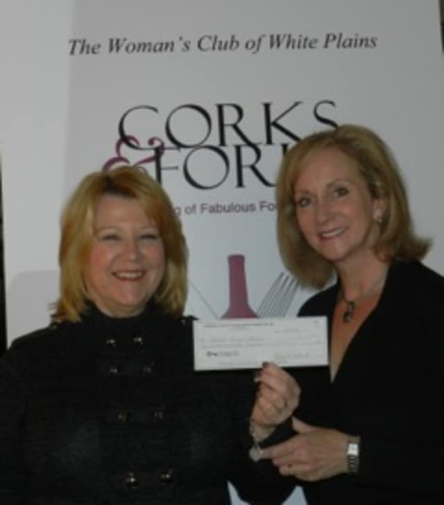 Maryann Martin, chairwoman of the Woman's Club of White Plains  Cork's & Forks event presents Kathleen Bonistall of PEACE OUTside Campus with a check for $7,500.