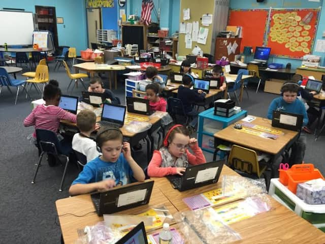 Students in Mary Fanning's first-grade class work on reading software on the first day of the mobile-learning program pilot.