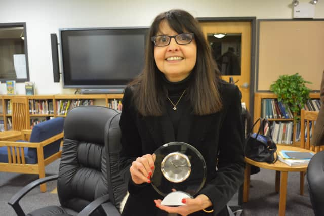 MaryJo Hauser poses for a photo with a gift that she received at the school board's Jan. 7 meeting.